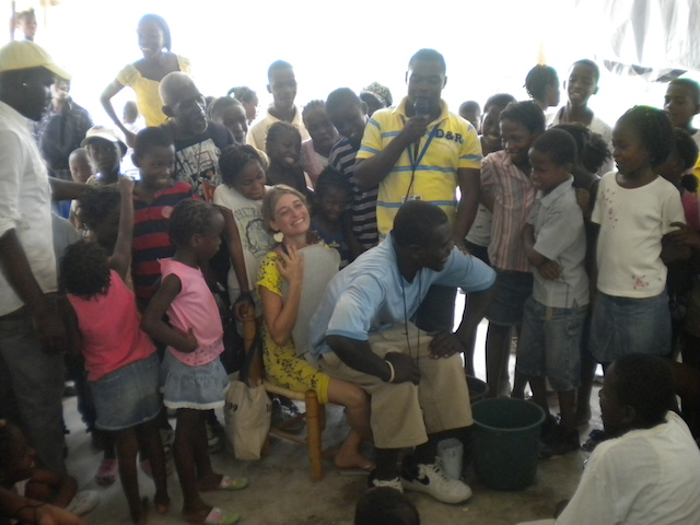 Sasha plays the role of a toilet in an educational workshop at the opening of a new SOIL toilet in Port-au-Prince.