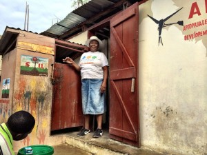 Madame Bwa standing in the doorway of one of SOIL's public toilets built in 2007.
