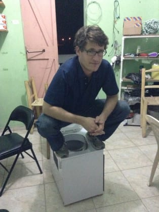 Lead author Kory Russel testing to make sure the toilet design is sturdy at SOIL's office in Cap Haitien.
